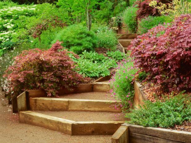 Terasovitá okrasná zahrada ve svahu s dřevěnou cestičkou