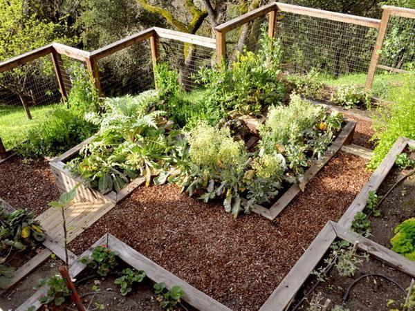 Terasovitá okrasná zahrada ve svahu s dřevěnými zídkami