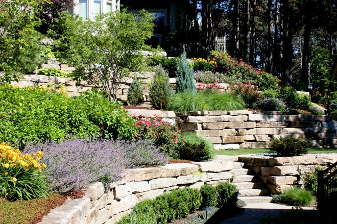 Terasovitá okrasná zahrada ve svahu s kamennými zídkami